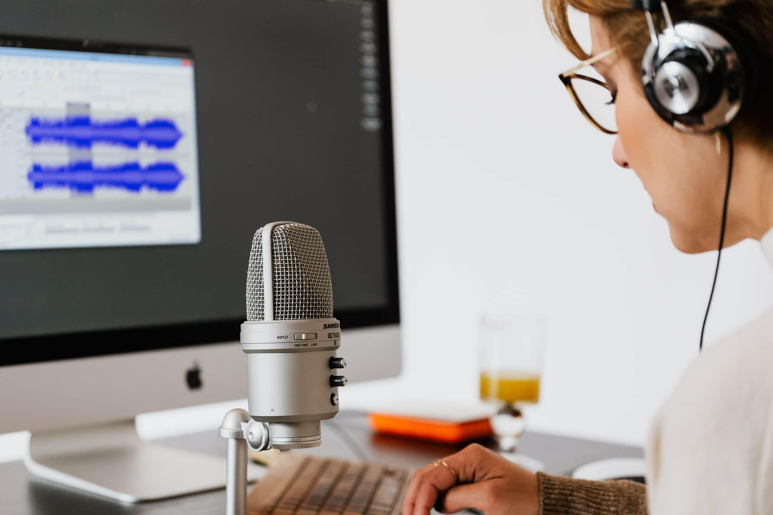 Eine Frau im Tonstudio nimmt einen Podcast auf.