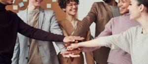 Menschen stehen in einem Kreis und haben die Hände in der Mitte zusammengelegt (Zeichen von Teamwork und Zusammenhalt)