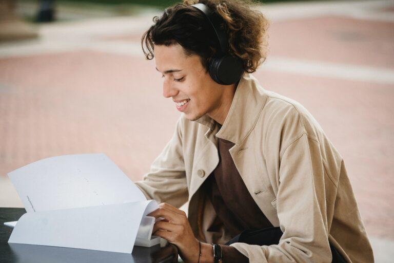 Eine Frau sitzt lächelnd auf dem Boden, hat schwarze On-Ear Kopfhörer auf und liest sich etwas durch