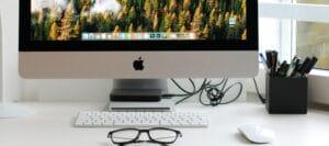 Ein Arbeitsplatz mit Bildschirm, Brille und Stiften