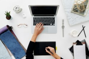 Eine Person sitzt am Schreibtisch mit dem Laptop, Handy und Tablet gleichzeitig. Das Bild soll Multitasking verdeutlichen
