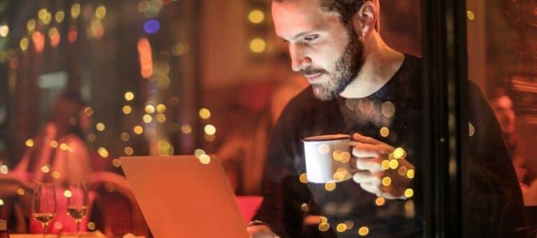 Mann sitzt mit einer Kaffeetasse vor einem Laptop in einem Café