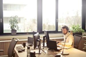 Ein Mann sitzt mit Kopfhörern an seinem Schreibtisch und arbeitet.