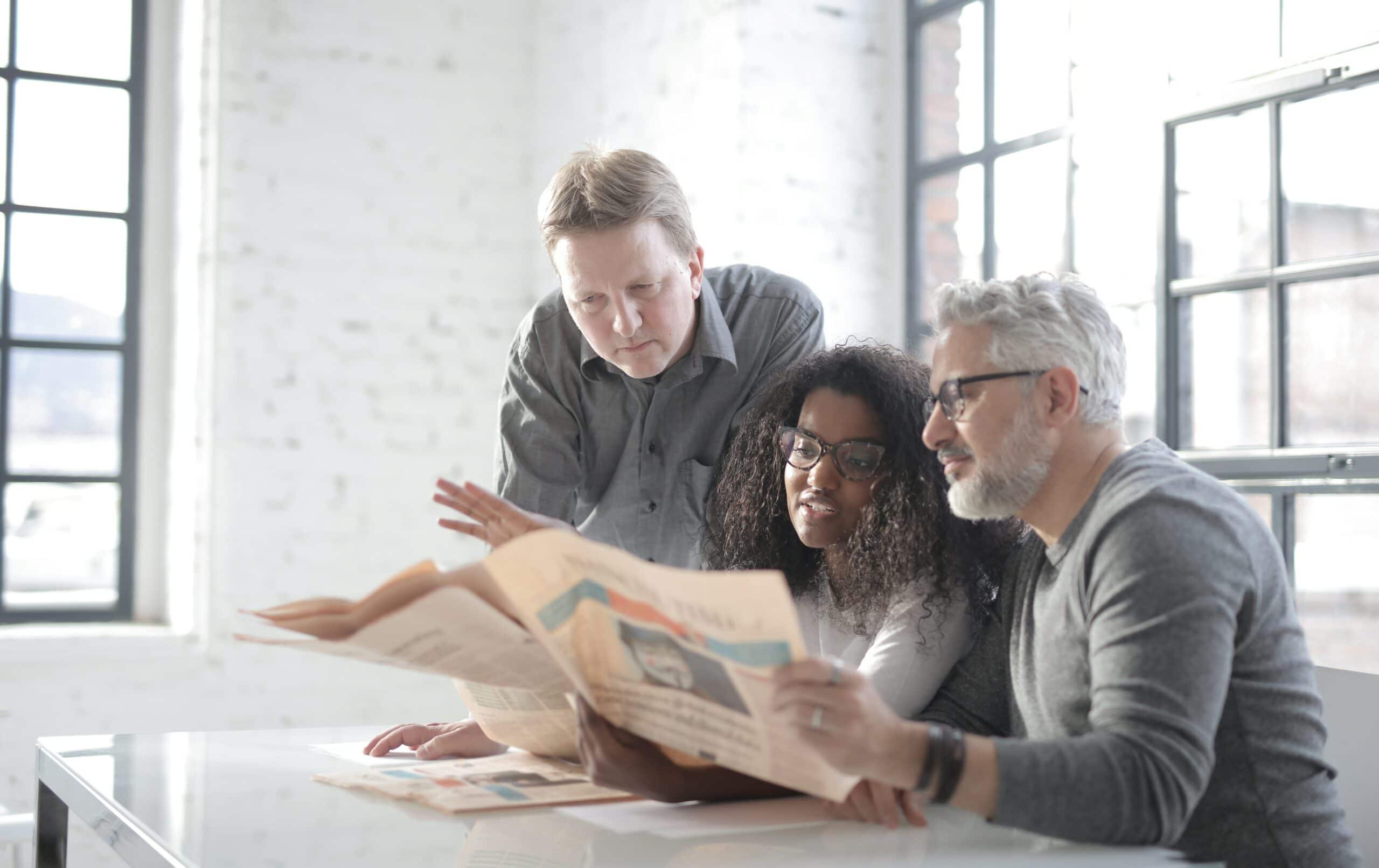 Zwei Männer und eine Frau sitzen in einem Raum und lesen gemeinsam eine Pressemeldung in der Zeitung.