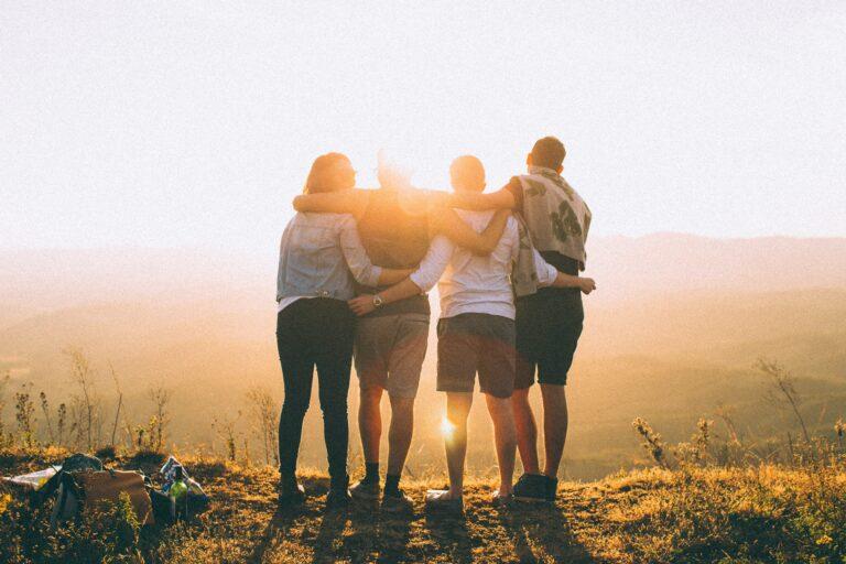 Vier Freunde stehen Arm in Arm auf einem Berg im Sonnenuntergang.