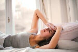 Eine Frau mit Schlafstörungen liegt im Bett und hält sich die Hand an den Kopf.