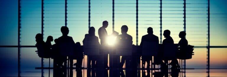 Viele Personen einer Firma sitzen zusammen an einem Tisch.