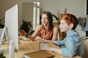 Eine Frau und ihr Kind sitzen zusammen vor dem Computer und lösen Aufgaben.