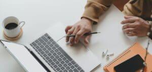 Eine Person arbeitet an einem Laptop, welches zusammen mit einem Notizbuch und einer Kaffeetasse auf dem Tisch steht.