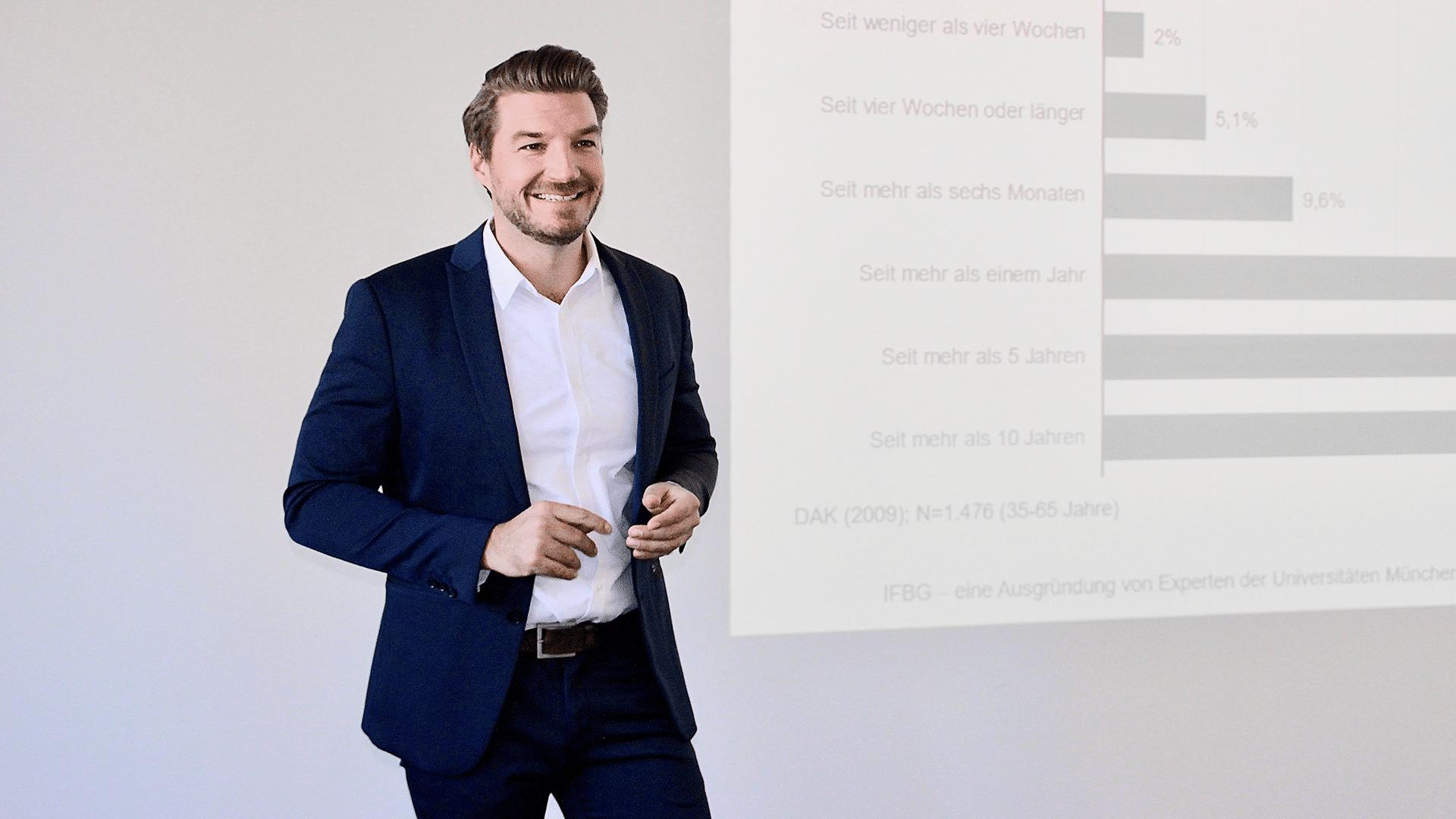 Dr. Fabian Krapf steht vor einer Wand, an der eine Grafik angezeigt wird