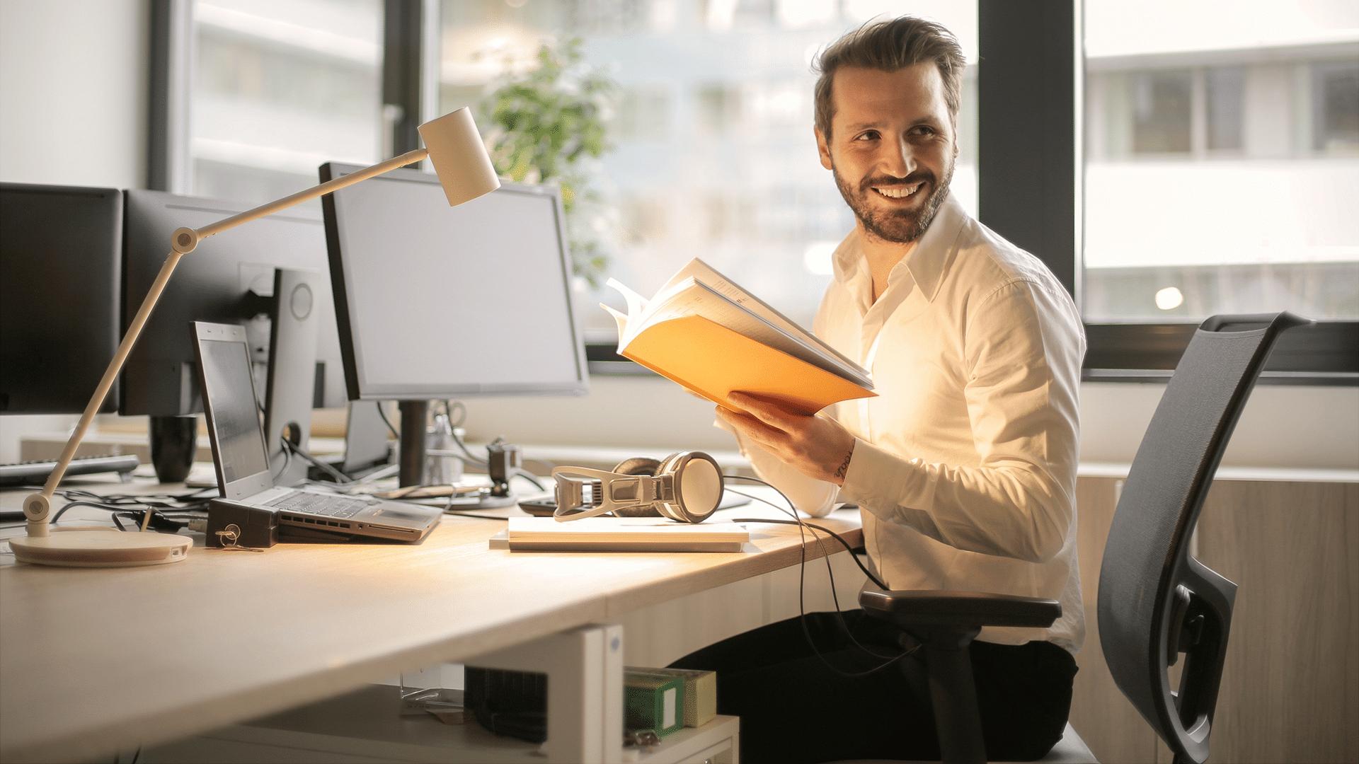 Ein Mann sitzt auf einem Bürostuhl und dreht sich lächelnd um