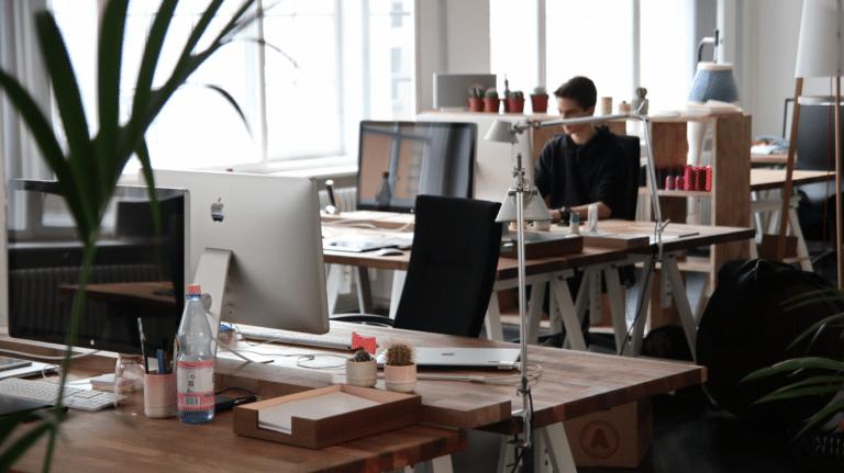 Ein junger Mann mit braunen Haaren und einem schwarzen Pullover sitzt in einem Großraumbüro am Schreibtisch und arbeitet.
