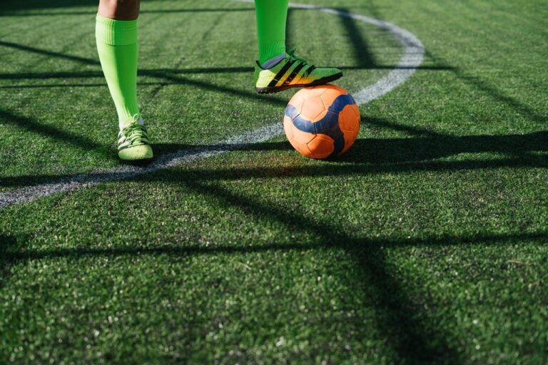 Fussballer mit Fuß auf einem Ball auf dem Fussballfeld