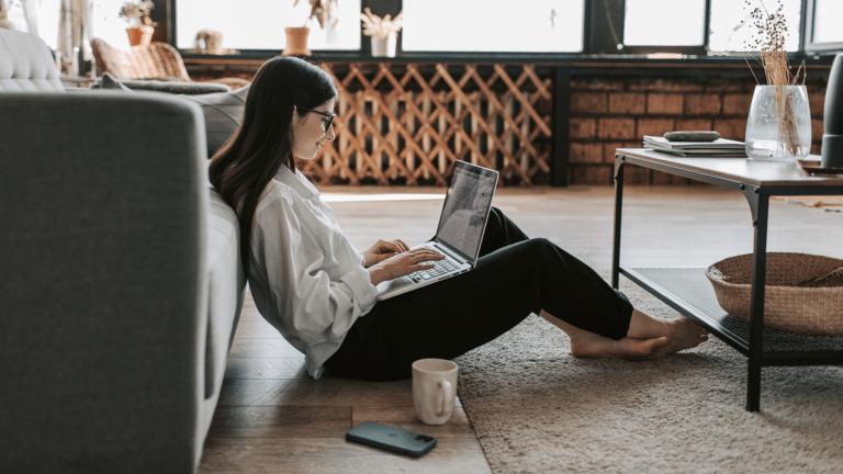 Eine Frau mit dunklen Haaren, Brille, einer weißen Bluse und einer schwarzen Hose sitzt in ihrem Home-Office am Laptop auf dem Boden im Wohnzimmer. Das Laptop steht auf ihren Beinen. Neben ihr liegt ihr Smartphone und dort steht ein weißer Becher mit Kaffee.