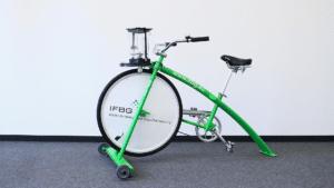 Shmoothie-Bike oder auch Shake-Bike genannt vor einer weißen Wand. Das Bike ist grün und hat nur vorne zwei Räder sowie eine Smoothie-Halterung. Es wird bei Maßnahmen des IFBG im Bereich Bewegung und Ernährung verwendet.