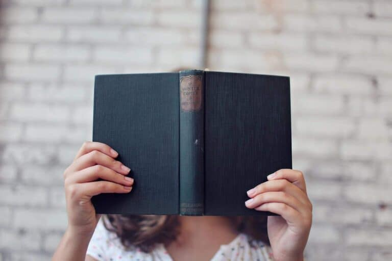 Eine Frau hält ein blaues Buch vor ihr Gesicht und liest etwas. In dem Buch stehen die wichtigsten Begriffe zum Betrieblichen Gesundheitsmanagement. Diese wurden durch das IFBG aufgegliedert und definiert.