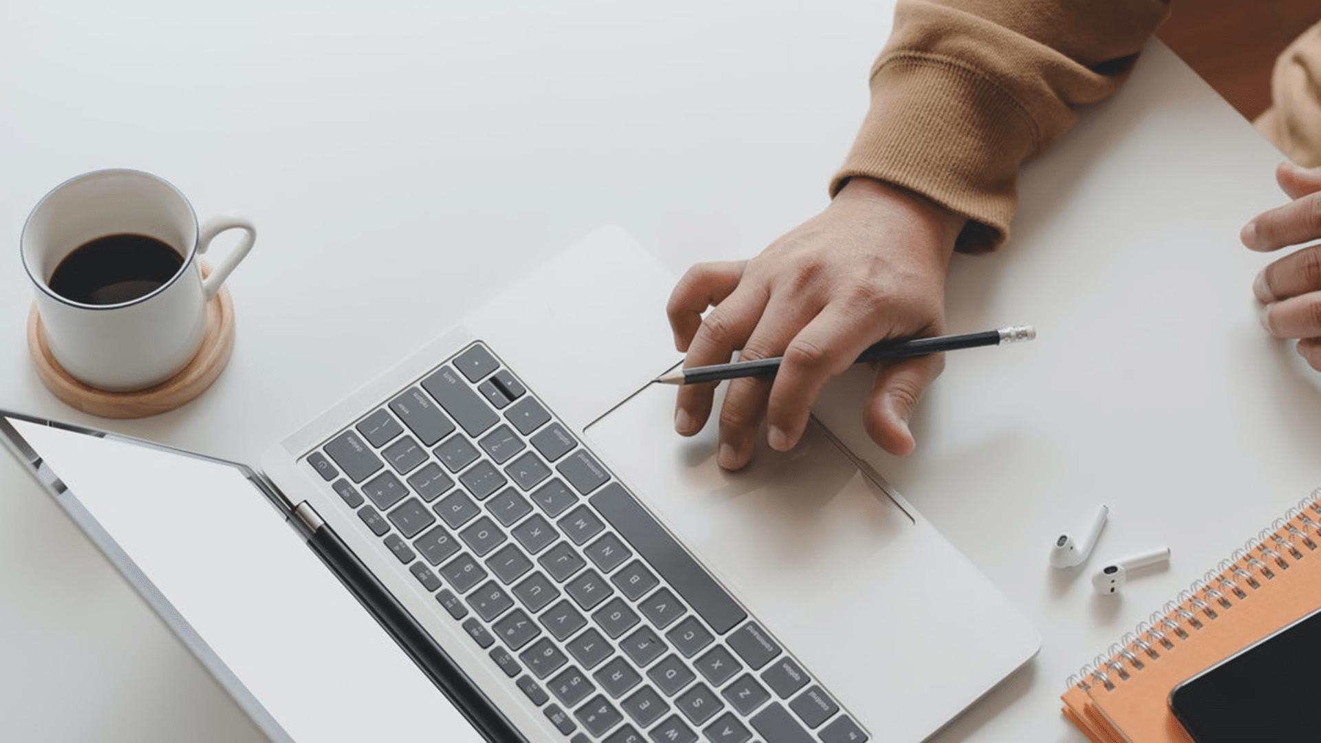 Eine Hand klickt auf einem Laptop etwas ein