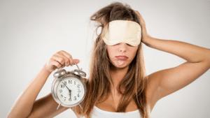 Frau mit Schlafmaske hält Wecker in der Hand