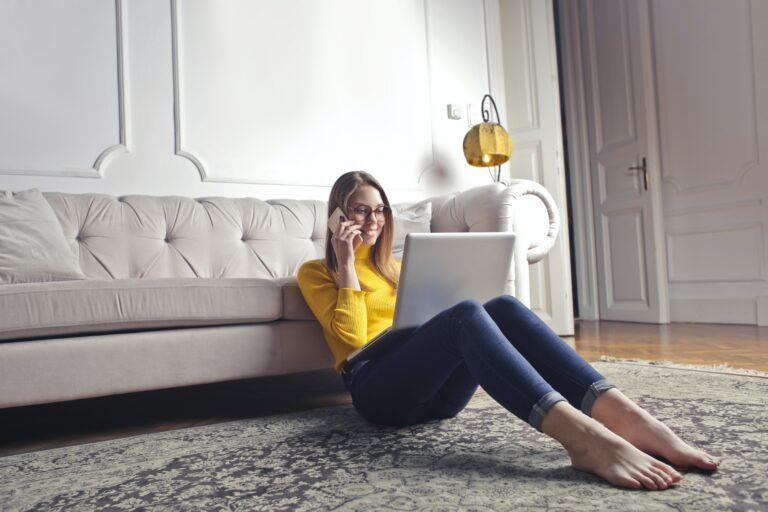 Frau sitzt auf Teppich und telefoniert mit Laptop auf dem Schoß