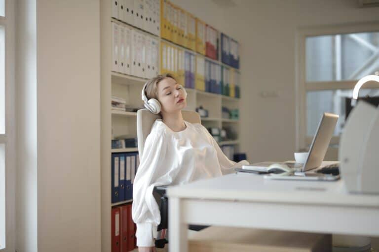Eine Frau trägt eine weiße Bluse und weiße On-Ear-Kopfhörer. Sie sitzt an ihrem Laptop, hat sich aber nach hinten gelegt und schläft.