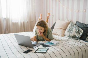 Eine blonde Frau mit einem grünen T-Shirt und einer weißen Hose liegt auf einem Bett und arbeitet am Laptop. Neben ihr liegen ein Notizbuch, ein Smartphone und ein Tablet.