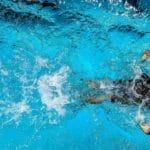 Ein Mann mit Badehose und Schwimmkappe schwimmt sportlich im Pool