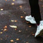 Joggerin läuft in weißen Turnschuhen auf nassem Boden mit Laubblättern