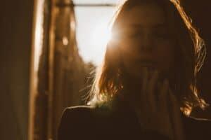 Eine Frau mit geschlossenen Augen ist der Kamera zugewand, Im Hintergrund scheint ihr die Sonne auf den Rücken